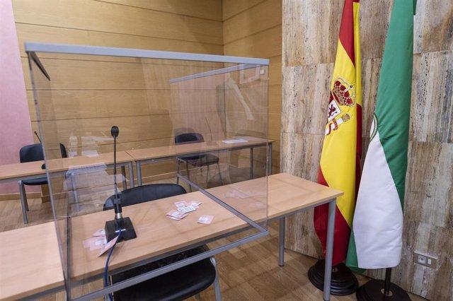 Sala de vistas de un juzgado andaluz con mampara instalada ante el Covid-19
