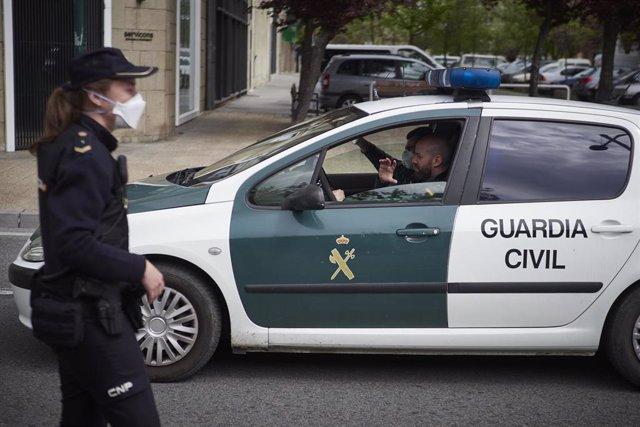Un vehículo de la Guardia Civil pasa junto a un control de la Policía Nacional en la Avenida del Ejército de Pamplona durante el día en el que se reactiva la actividad laboral no esencial en las empresas cuyos empleados no puedan teletrabajar cuando se cu