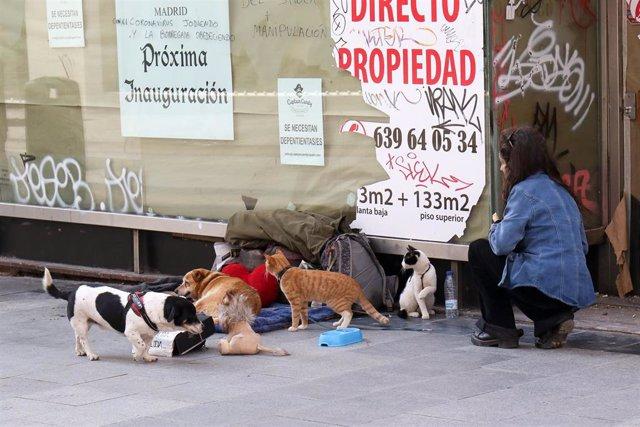 Una mujer observa a una persona sin hogar en la calle de Madrid durante la crisis del coronavirus a 15 de marzo de 2020.