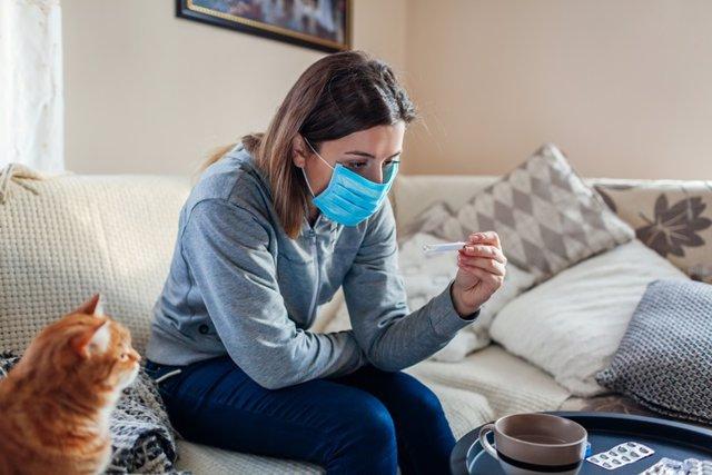 Mujer tomándose la temperatura con un termómetro. Coronavirus, Covid-19.