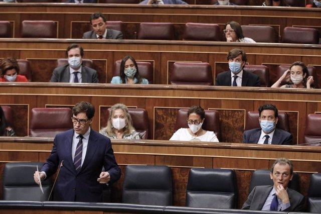 La vicepresidenta primera, Carmen Calvo, habla con el presidente del Gobierno, Pedro Sánchez, durante una sesión plenaria en el Pleno del Congreso en la que se votan las medidas de política social pactadas en el senado de la Comisión para la Reconstrucció