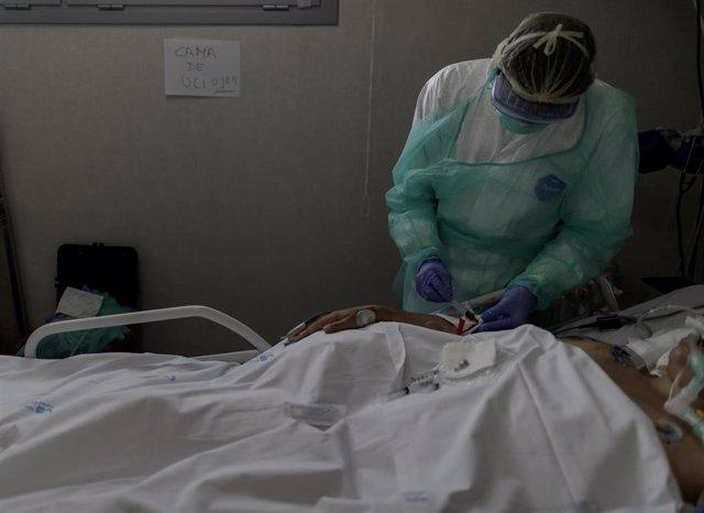 Personal sanitario totalmente protegido atiende a un paciente ingresado en la Unidad de Cuidados Intensivos del Hospital Infanta Sofía en San Sebastián de los Reyes (Madrid). En San Sebastián de los Reyes, Madrid, (España), a 28 de abril de 2020.