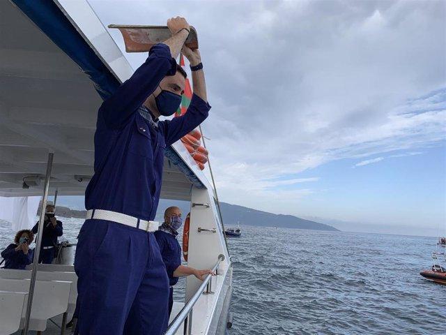 El alcalde de Bermeo, Aritz Abaroa, lanza la teja, con la isla de Izaro a sus espaldas, confirmando los límites de la localidad.