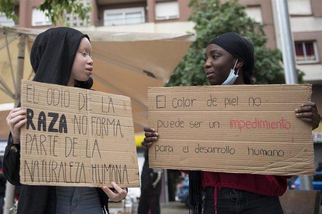 Dos participantes en la concentración de la Comunidad Negra Africana y Afrodescendiente en España (CNAAE) contra el racismo, a 7 de junio de 2020.