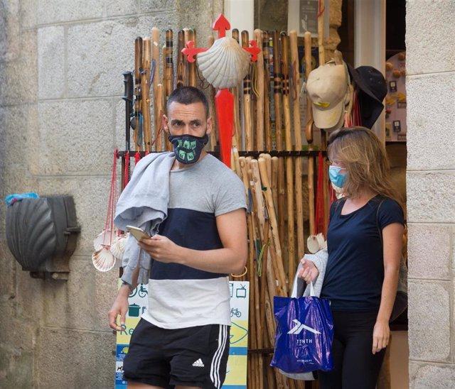 Los peregrinos alicantinos Miguel Ángel y Elena salen de un establecimiento con elementos del Camino a la venta en la localidad de Sarria, mientras los peregrinos retornan al Camino francés de la Ruta Jacobea