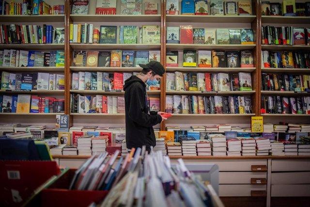 Un jove observa un llibre de la papereria Donem. A Barcelona, Catalunya, (Espanya), a 22 d'abril de 2020 (arxiu).