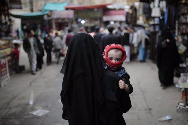 Una mujer con su hijo en un mercado de la capital de Yemen, Saná