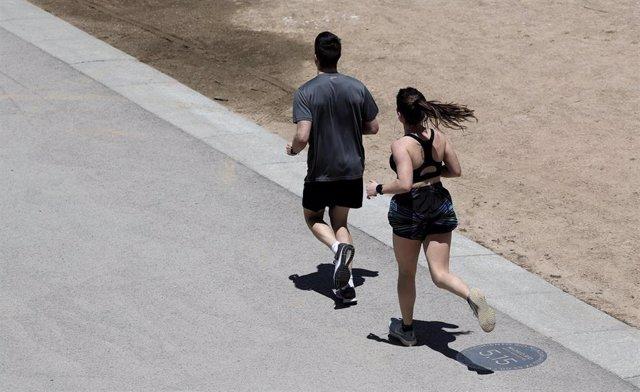Dos personas corren por un parque