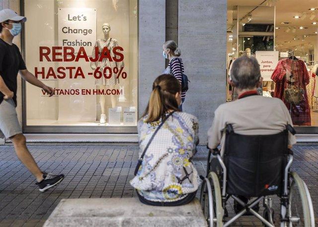 Varias personas pasan al lado del escaparate de una tienda donde se observan carteles indicativos de rebajas en Valencia, Comunidad Valenciana (España) a 3 de julio de 2020.