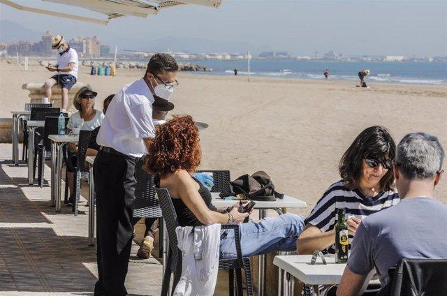 Varias personas disfrutan en la terraza de un bar junto a la playa después de que el Ministerio de Sanidad autorizara a que la totalidad de la Comunidad Valenciana pasase en su conjunto a la fase 1 de la desescalada.