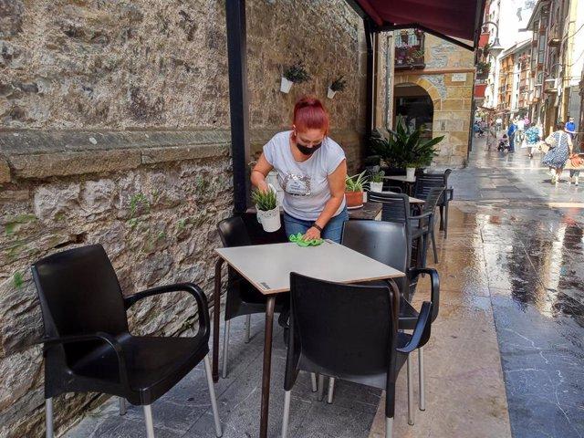 Una trabajadora desinfecta la mesa de la terraza de uno de los locales hosteleros que han vuelto a la fase 2 tras las limitaciones impuestas por el Gobierno Vasco. En Ermua, Vizcaya, País Vasco, (España), a 21 de julio de 2020.
