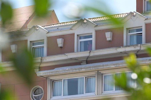 Una persona mira por una ventana del hotel NH Finisterre de A Coruña donde los jugadores del CF Fuenlabrada permanecen confinados en él tras haber dado positivo en coronavirus varios de sus miembros