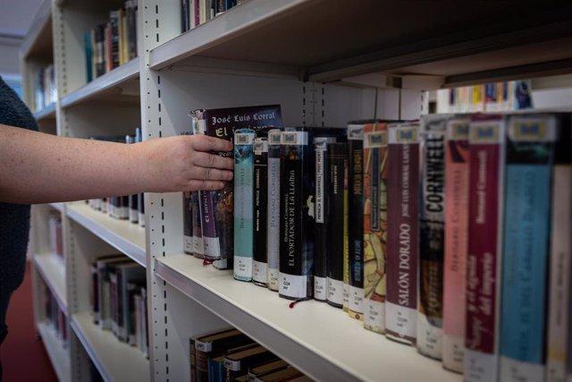 Una bibliotecaria coge un libro de una estantería de la Biblioteca municipal del Centro Cívico Ibaiondo en Vitoria-Gasteiz tras su reapertura