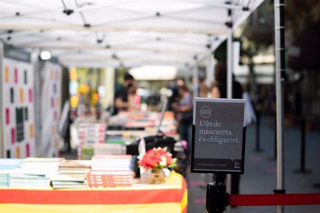 Varios personas observan libros en varios puestos de libros colocados en la calle, en Barcelona, Catalunya (España), a 23 de julio de 2020.