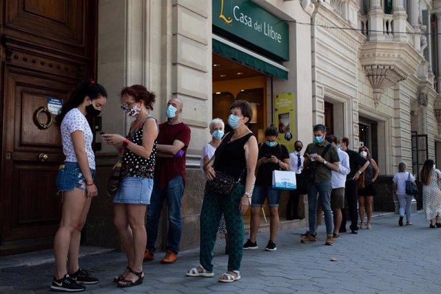 Decenas de personas protegidas con mascarilla hacen cola para entrar en una biblioteca, en Barcelona, Catalunya (España), a 23 de julio de 2020. Cataluña celebra este jueves un Día del Libro y de la Rosa aplazado tras no poder celebrarlo el pasado 23 de a