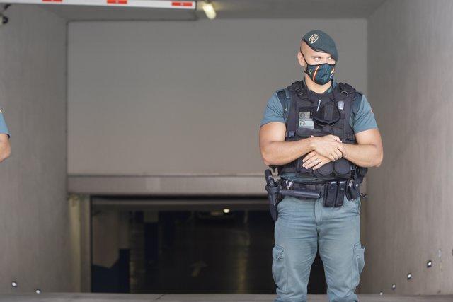 Un agente de la Guardia Civil vigila la llegada en coche del presidente de la Autoritat Portuària de Baleares (APB), Joan Gual de Torrella