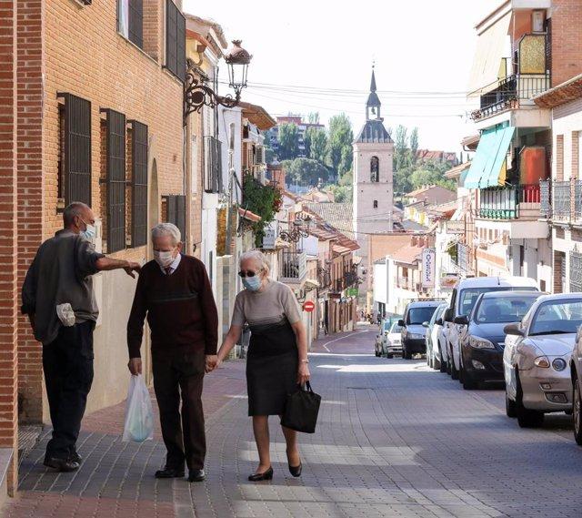 Una pareja anda por la calle de un pueblo