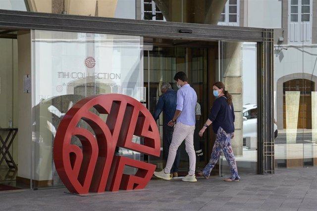 Dos personas entran por la puerta del hotel NH Finisterre de A Coruña donde jugadores del CF Fuenlabrada permanecen confinados tras dar positivo en COVID-19