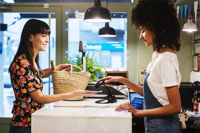 Cliente pagando con su smartphone en una tienda
