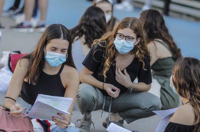 Estudiantes de bachillerato sentados en las instalaciones exteriores minutos antes de entrar a las aulas para realizar los exámenes Selectividad o Pruebas de Acceso a la Universidad.