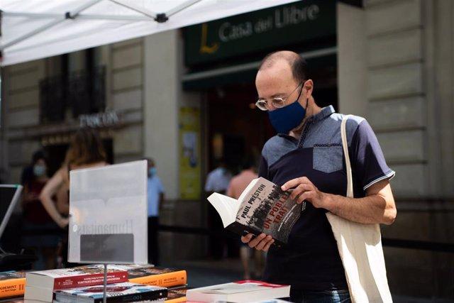 Un hombre hojea un libro en un puesto de libros colocado en la calle, en Barcelona, Catalunya (España), a 23 de julio de 2020. (archivo)