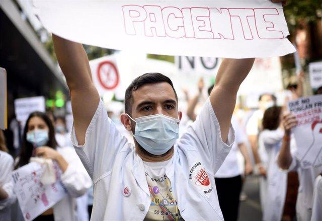 Un médico residente de la Comunidad de Madrid levanta una pancarta en la que se lee 'paciente' durante una manifestación, hoy lunes, justo cuando se cumple una semana de huelga indefinida, para reclamar un convenio colectivo ante la negativa de la Conseje