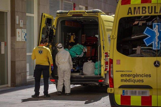Dos sanitarios en la puerta de una ambulancia en la que hay un paciente contagiado con coronavirus en el Centro de Emergencias de Atención Primaria Pere Camps en el Raval, durante el traslado de personas de colectivos vulnerables desde este centro a hotel