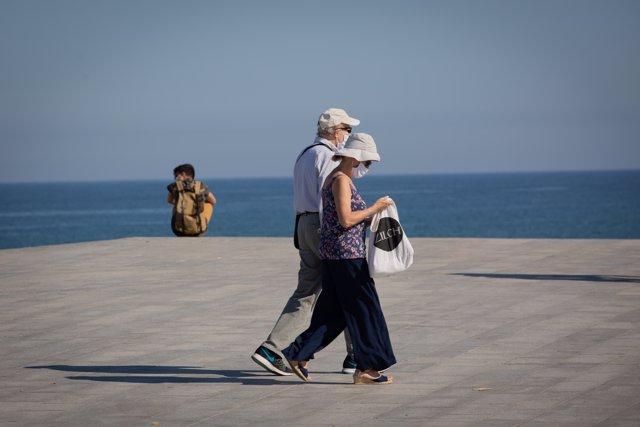 Dos personas protegidas con mascarillas pasean por el Paseo Marítimo de la Playa de la Barceloneta