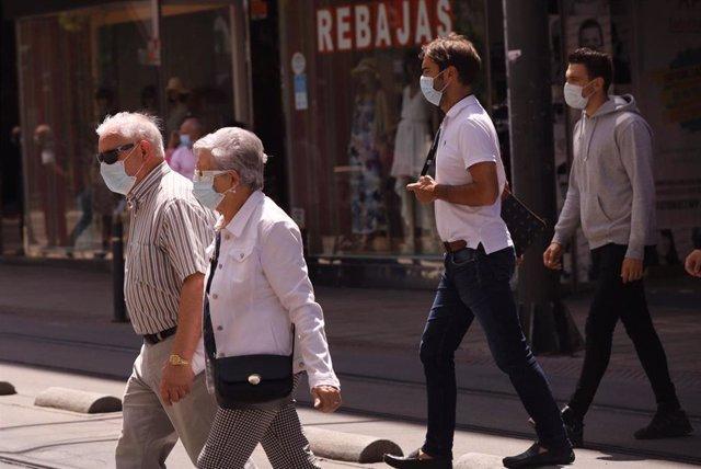 Varias personas pasean con mascarilla.