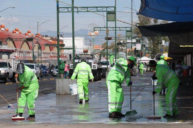Varios trabajadores limpiando las calles por el coronavirus.