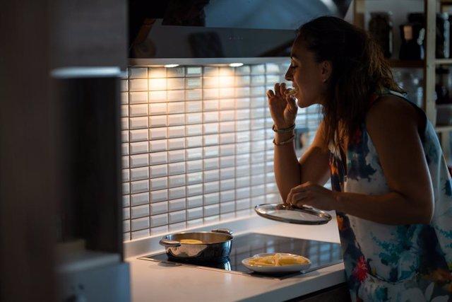 Mujer comiendo de noche en la cocina.