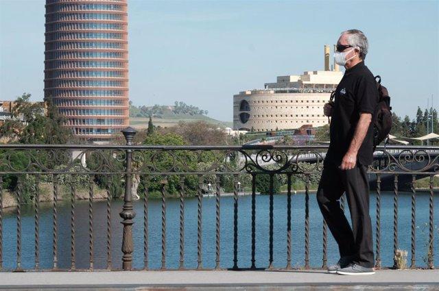 Una persona protegida con mascarilla pasea por el puente de Triana.