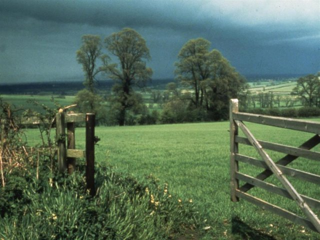 A country scene taken against a stormy sky.