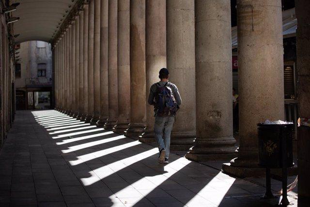Un home camina per un carrer de Barcelona.
