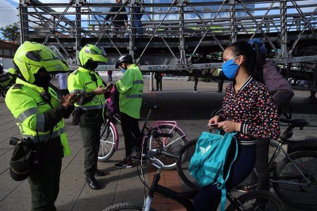 Varios agentes revisan la documentación de una mujer en bicicleta con mascarilla por el coronavirus.