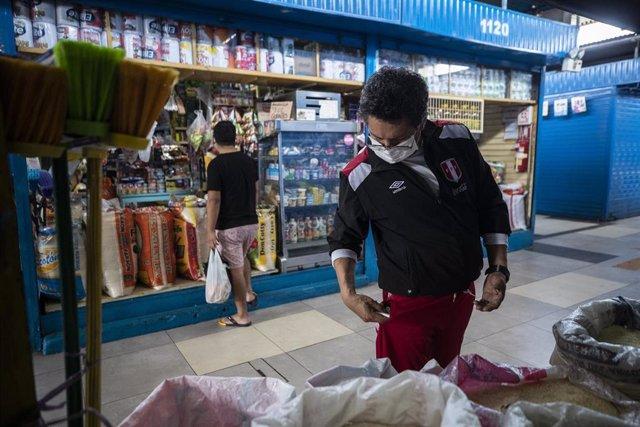 Un hombre con mascarilla por el coronavirus en un mercado en Lima.