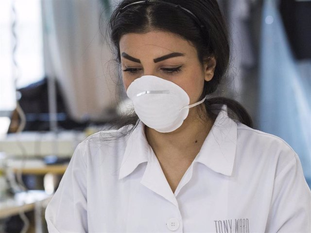 A seamster gathers up medical face masks to place in a package at the Tony Ward Couture fashion house on March 26, 2020 in Beirut, Lebanon.