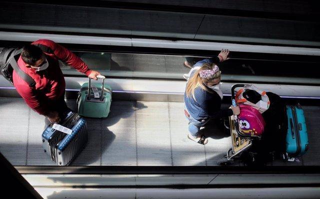 Pasajeros con maletas en la terminar T4 del Aeropuerto Adolfo Suárez Madrid Barajas, en Madrid
