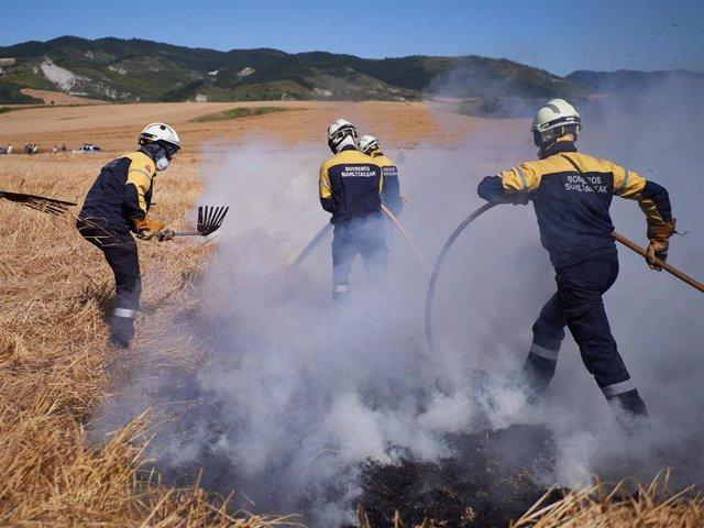 Varios bomberos realizan labores de extinción de un incendio forestal producido en una zona de campo de cereal, sin afectar a zonas urbanas, cerca de la localidad navarra de Sarriguren, a 21 de junio de 2020.