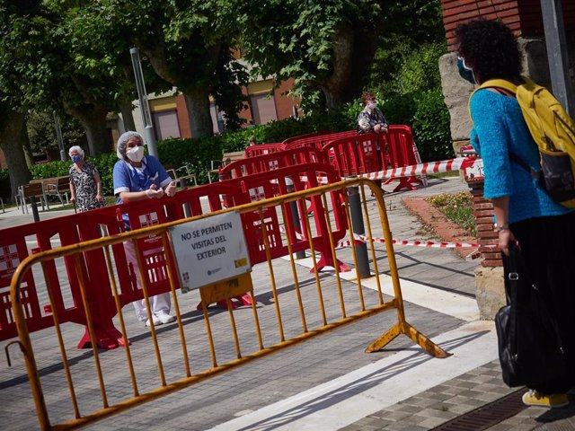 Una trabajadora sanitaria de la 'Casa de Misericordia' protegida con mascarilla habla con una mujer en el exterior del centro donde han habilitado una zona de visitas para residentes y familiares. En Pamplona (Navarra), a 2 de junio de 2020.