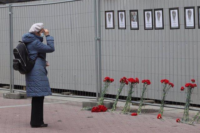 Una mujer ante un muro en el que se rinde homenaje a los trabajadores sanitarios fallecidos por el coronavirus en San Petersburgo