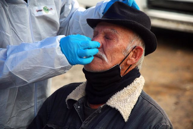 A health worker takes a sample from a man at a rapid corona test station following the Chilean government decision to extend the strict exit restrictions to contain the spread of the coronavirus pandemic