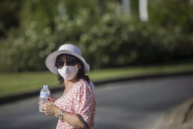 Una mujer, cubierta con sombrero, se refresca con agua.