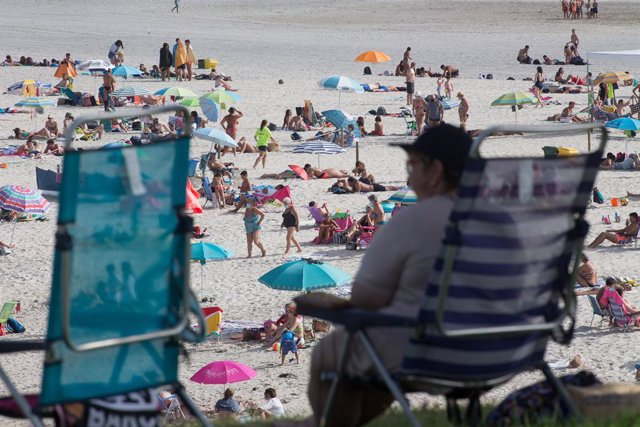 Una persona sentada frente a la playa en A Mariña (Lugo/Galicia) a 27 de julio de 2020.