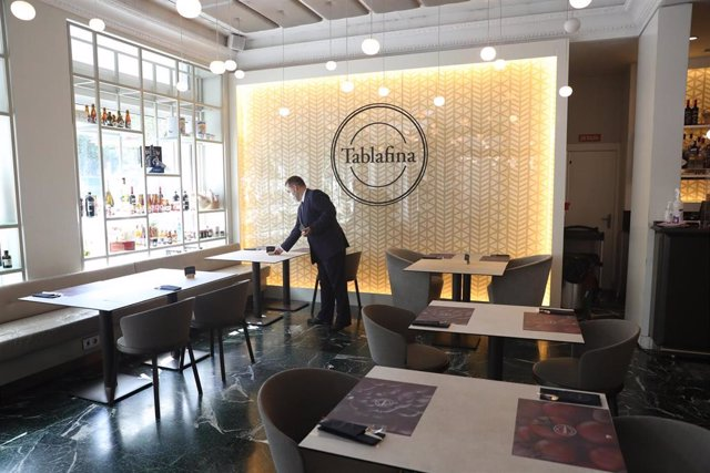 Un camarero prepara una mesa en el restaurante Tablafina en el Paseo del Prado durante la segunda fase de la nueva normalidad en la que el aforo permitido en las zonas comunes de los restaurantes aumenta hasta el 75%.