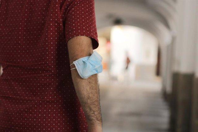 Un hombre lleva la mascarilla en el brazo en Mérida