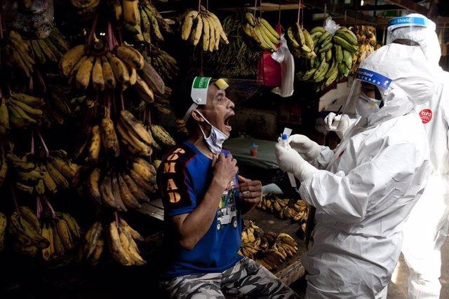 Un trabajador sanitario realiza una prueba de COVID-19 en Indonesia.