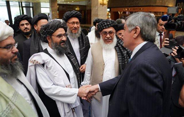El líder de la oficina política talibán en Qatar, el mulá Abdul Ghani Baradar, saluda a un alto cargo del Ministerio de Exteriores ruso en una reunión en Moscú