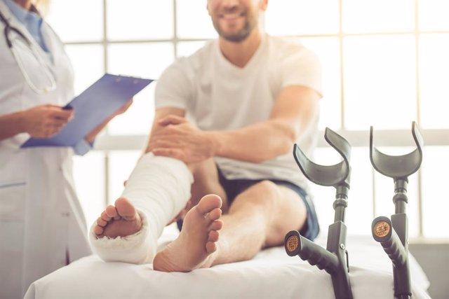 Hombre con una pierna escayolada y muletas, en la consulta del médico.