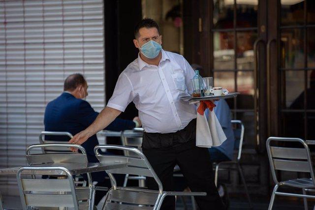 Un cambrer serveix a la terrassa d'un bar. Barcelona, Catalunya (Espanya), 26 de maig del 2020.